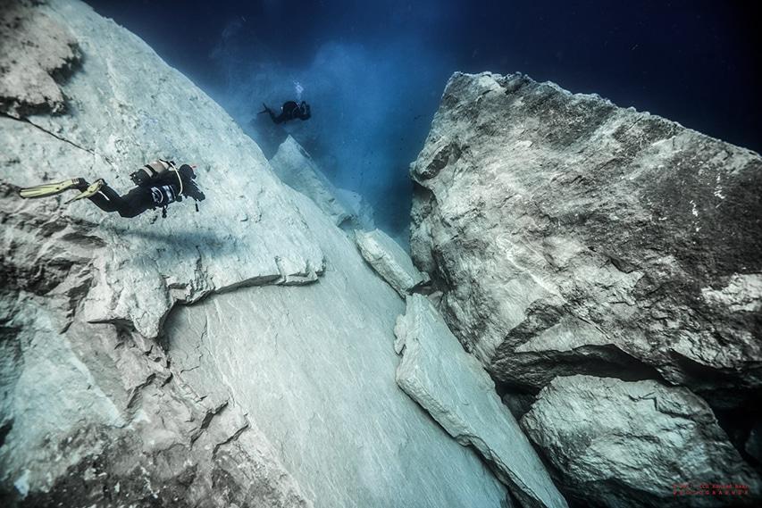 Nurkowie robią zdjęcia zawalonego łuku skalnego