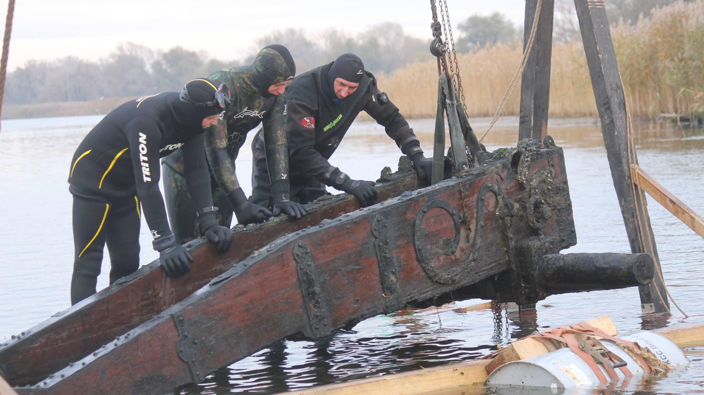 Archeolodzy badający lawetę armatnią wydobytą z wody