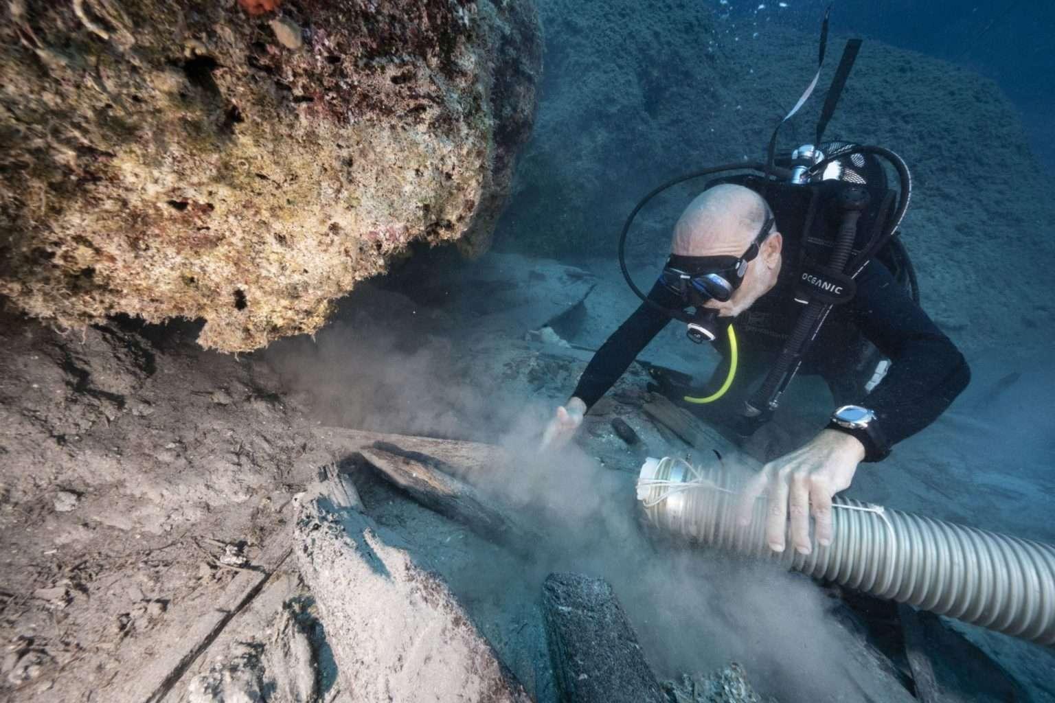 archeolog podwodny pracujący eżektorem