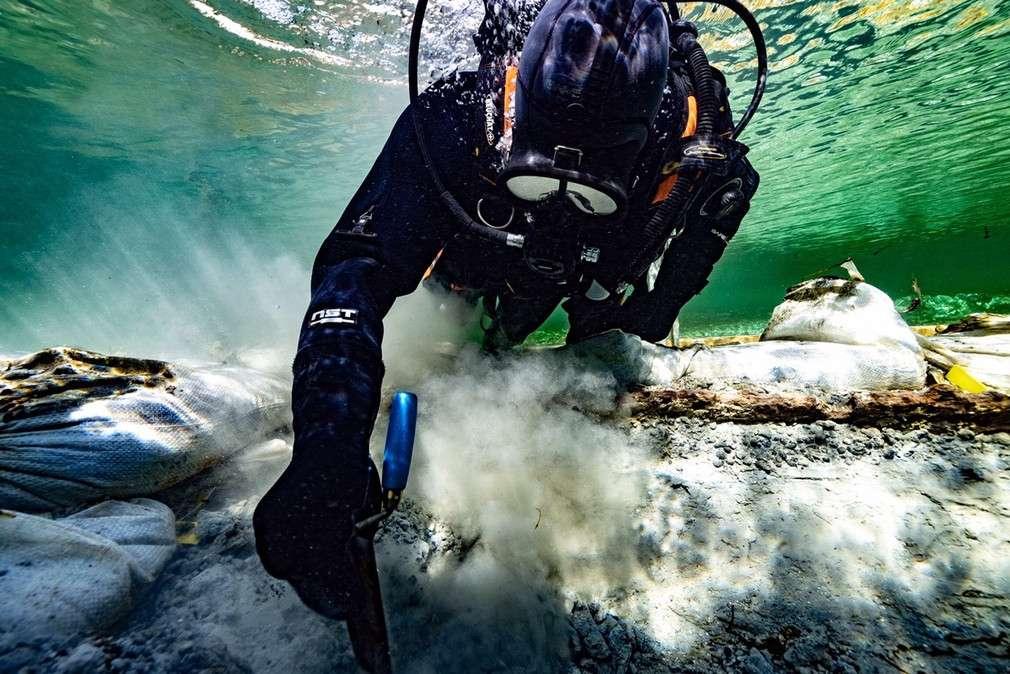 nurek archeolog odsłaniający wrak dłubanki sprzed 4000 lat