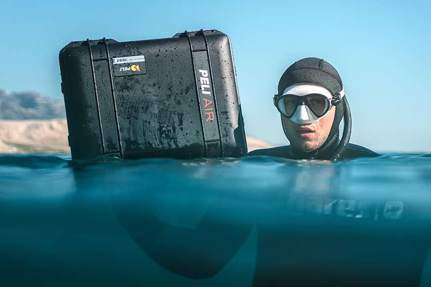 Freediver w wodzie ze skrzynią transportową PELI